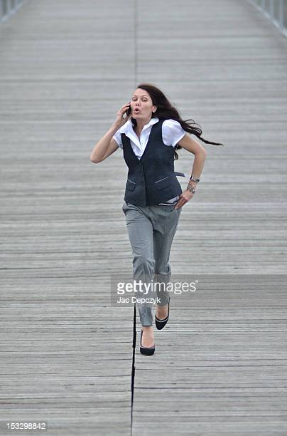Woman talking on the phone and running on a bridge