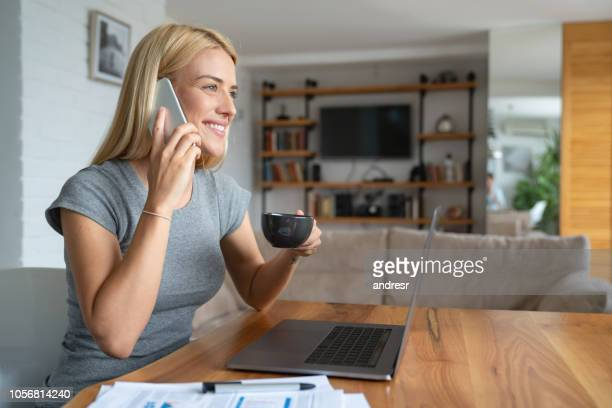 Woman talking on the phone at home while working