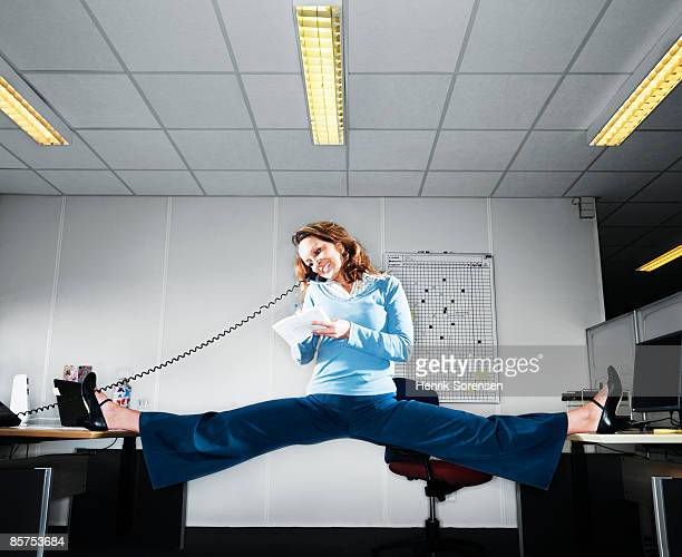 woman talking on the phone doing the splits betwee - doing the splits stock pictures, royalty-free photos & images