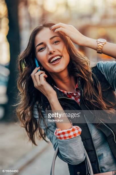 woman talking on the phone in the city - one young woman only stock pictures, royalty-free photos & images