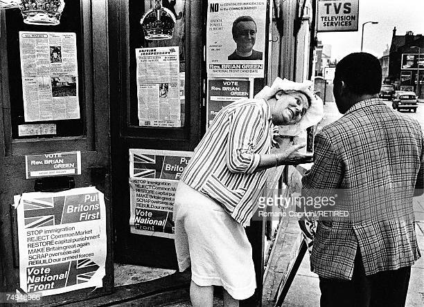 A woman talking to a black man by a doorway covered in general election posters urging support for the Reverend Brian Green the local candidate for...