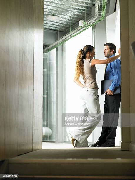 A woman talking to a man in a hallway