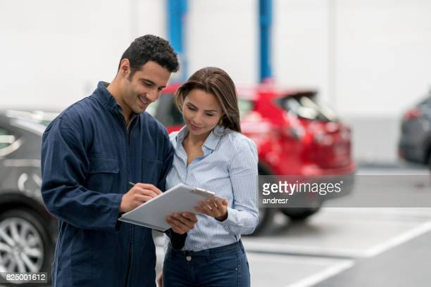 woman talking to a mechanic fixing her car - auto repair shop stock pictures, royalty-free photos & images