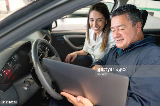 Woman talking to a mechanic in a car
