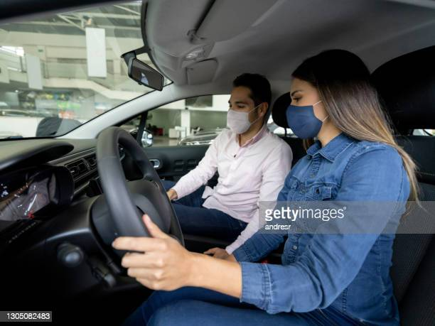 woman talking to a salesman and wearing facemasks while buying a car at the dealership - test drive stock pictures, royalty-free photos & images