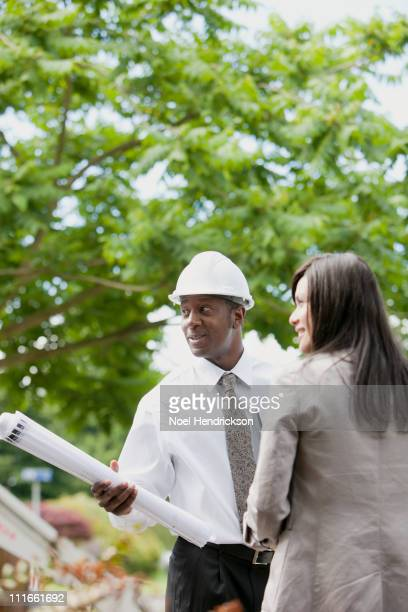Woman talking to architect holding blueprints