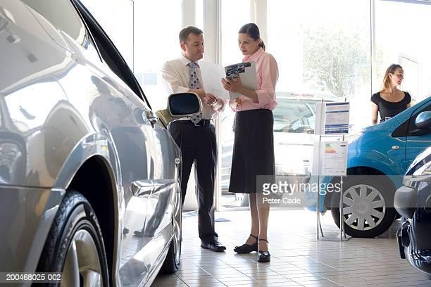Woman talking to auto salesman in showroom