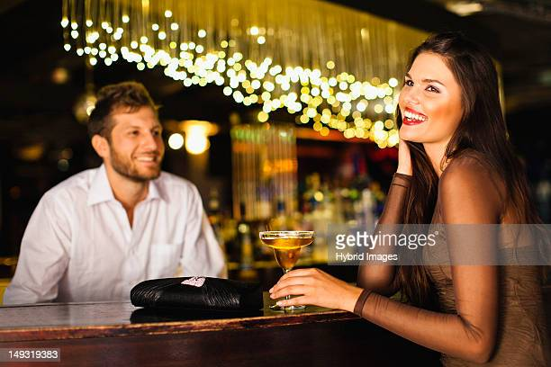 Woman talking to bartender at bar
