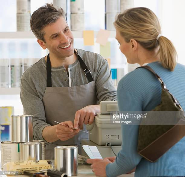 Woman talking to clerk at paint store