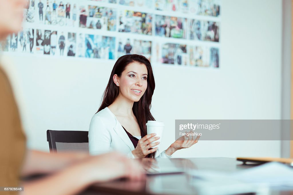 Woman talking to colleagues in design studio office meeting : Stock Photo