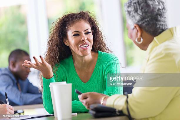 Woman talking to friend over coffee during therapy session