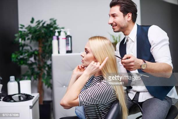 woman talking to hairdresser in hair salon - salon de coiffure photos et images de collection