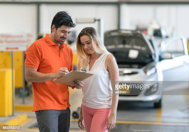 Woman talking to her mechanic at an auto repair shop