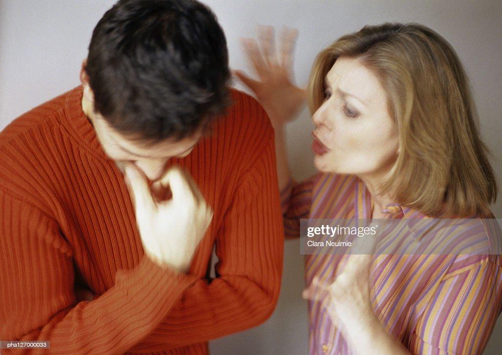 Woman talking to man looking down : Stockfoto