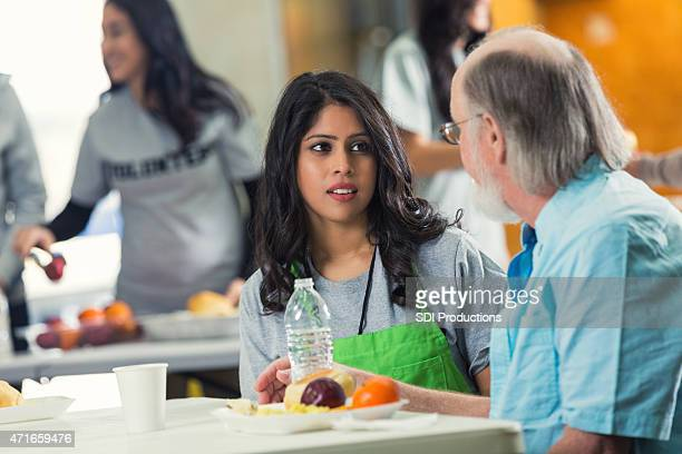 woman talking to senior man in food bank soup kitchen - depression bread line stock pictures, royalty-free photos & images