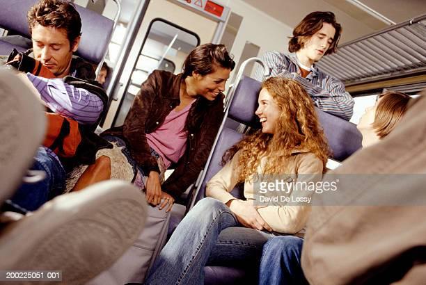 Woman talking to teenage girl (16-17 years) on train