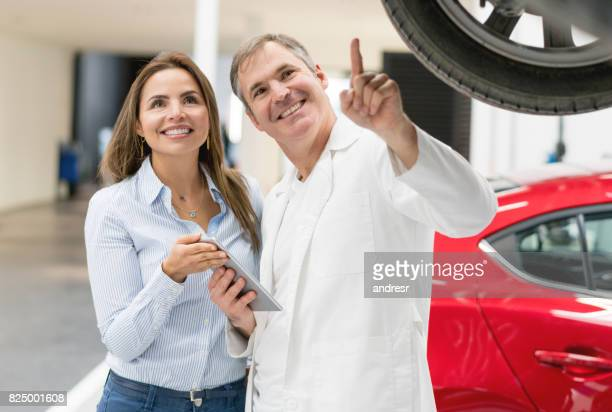 Woman talking to the mechanic about her car repair
