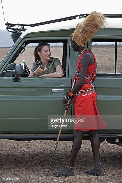 woman talking to tribesman - hugh sitton stock pictures, royalty-free photos & images