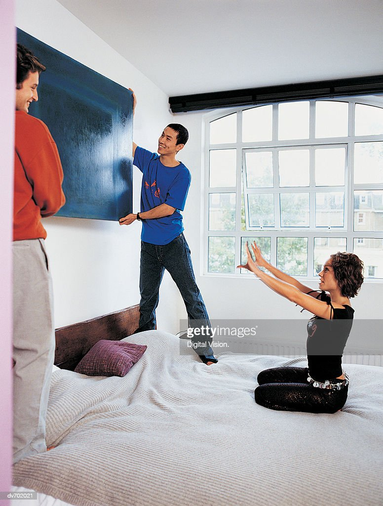Woman Talking to Two Men Hanging a Painting : Stock Photo