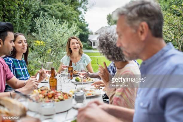 Frau im Gespräch beim Mittagessen mit Freunden