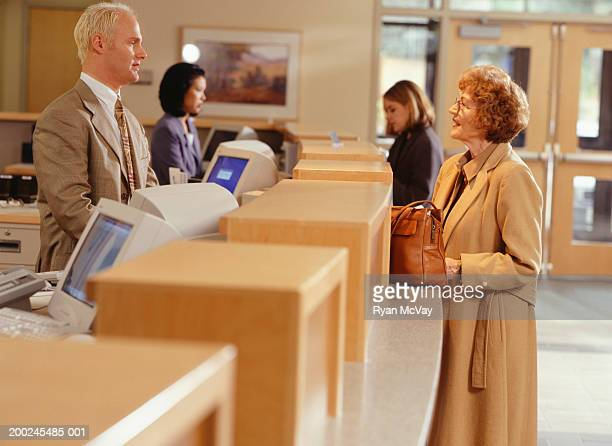 Woman talking with bank teller at reception desk, side view