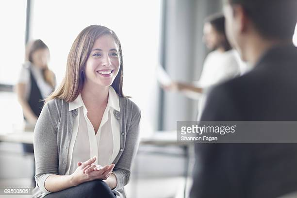 Woman talking with colleague in open studio room