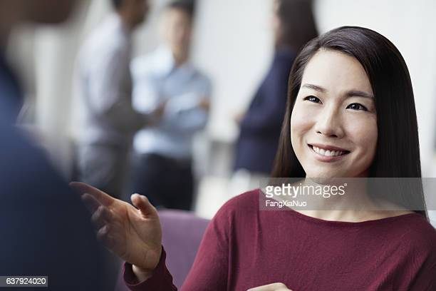 Woman talking with colleagues in office