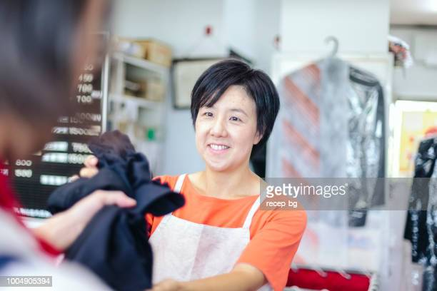 Woman talking with customer in dry cleaning shop