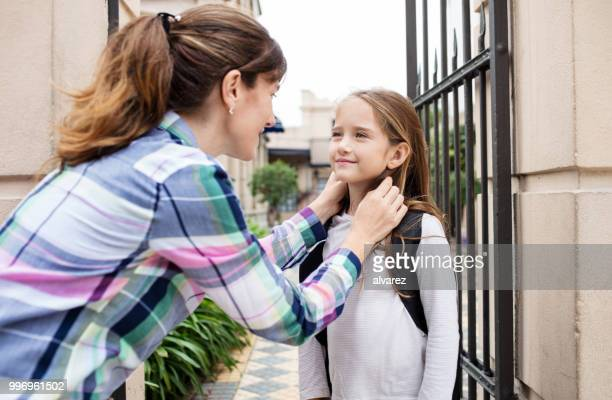 woman talking with daughter outside school gate - first day of school stock pictures, royalty-free photos & images