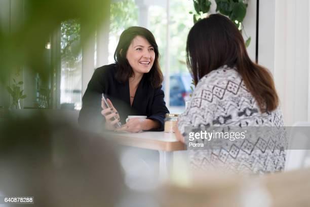 Woman talking with female friend in coffee shop