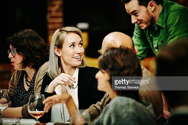 Woman talking with friends during dinner party