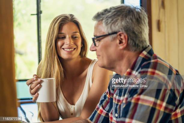 woman talking with her father - father daughter stock pictures, royalty-free photos & images