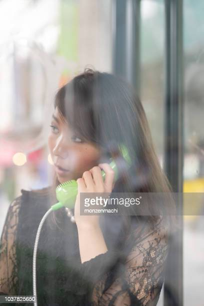 woman talking with retro-phone in telephone box - telephone booth stock pictures, royalty-free photos & images