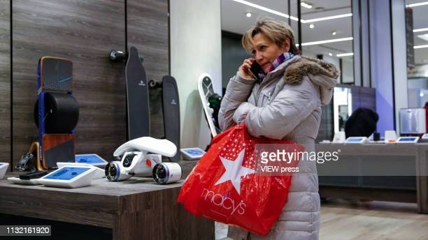 A woman talks by phone as she visits the Macy's headquarter on February 25 2019 in New York City Earnings reports of $253 is expected for Macy's Inc...