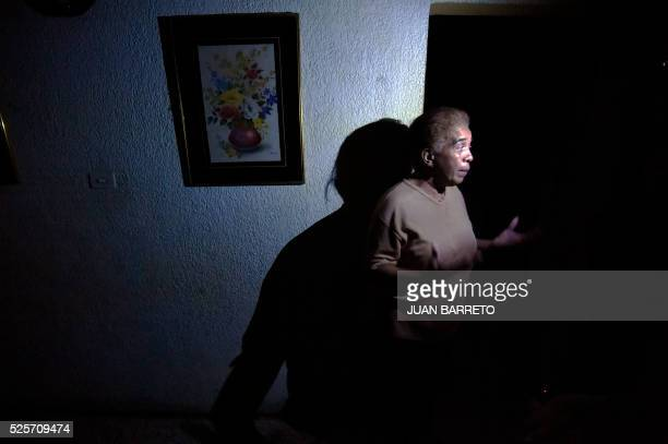 A woman talks inside her house during a power cut in Maracaibo city on April 28 2016 The political tension shortages and now enforced electricity...
