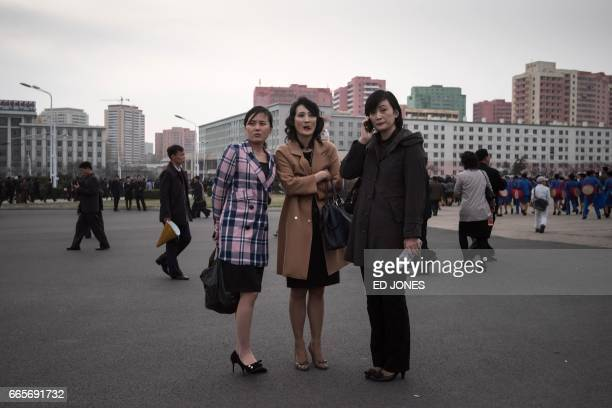 A woman talks on a mobile phone as she stands with others outside the Kim IlSung stadium after the AFC Women's 2018 Asian Cup Group B qualifying...