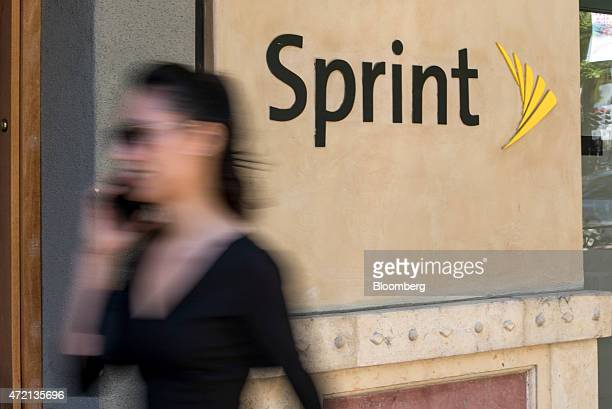 Woman talks on a mobile phone as she walks past a Sprint Corp. Store in Palo Alto, California, U.S., on Friday, May 1, 2015. Sprint Corp. Is...