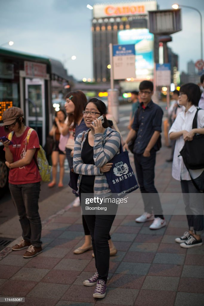 A woman talks on a mobile phone while waiting at a bus stop near Taipei Main Station in Taipei, Taiwan, on Wednesday, July 24, 2013. Taiwan President Ma Ying-jeou ruled out driving down the Taiwan dollar to boost exports following the currencys rally against the yen and said the government still aims for growth of at least 2 percent this year. Photographer: Jerome Favre/Bloomberg via Getty Images