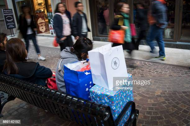 A woman talks on a smartphone as she sits next to shopping bags and a gift wrapped box in Hong Kong China on Saturday Dec 9 2017 With more Chinese...
