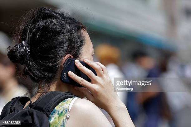 A woman talks on a smartphone in Tokyo Japan on Monday Sept 14 2015 NTT Docomo Inc led declines among Japanese wireless carriers plunging the most in...