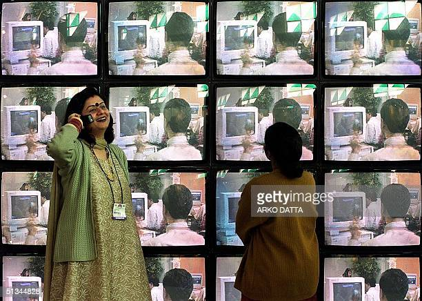 A woman talks on her cell phone as another stares at a multiscreen display at 'IT Asia 2000' an Information Technology expo 08 February 2000 in New...