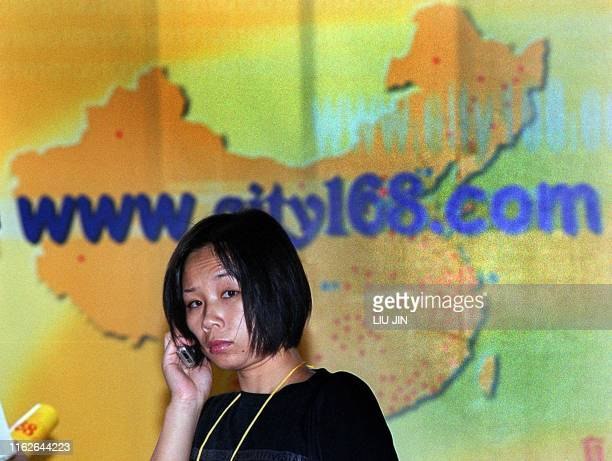 A woman talks on her mobile phone in front of a website poster promoting a sales network around the whole of China at the China Websites Exhibition...
