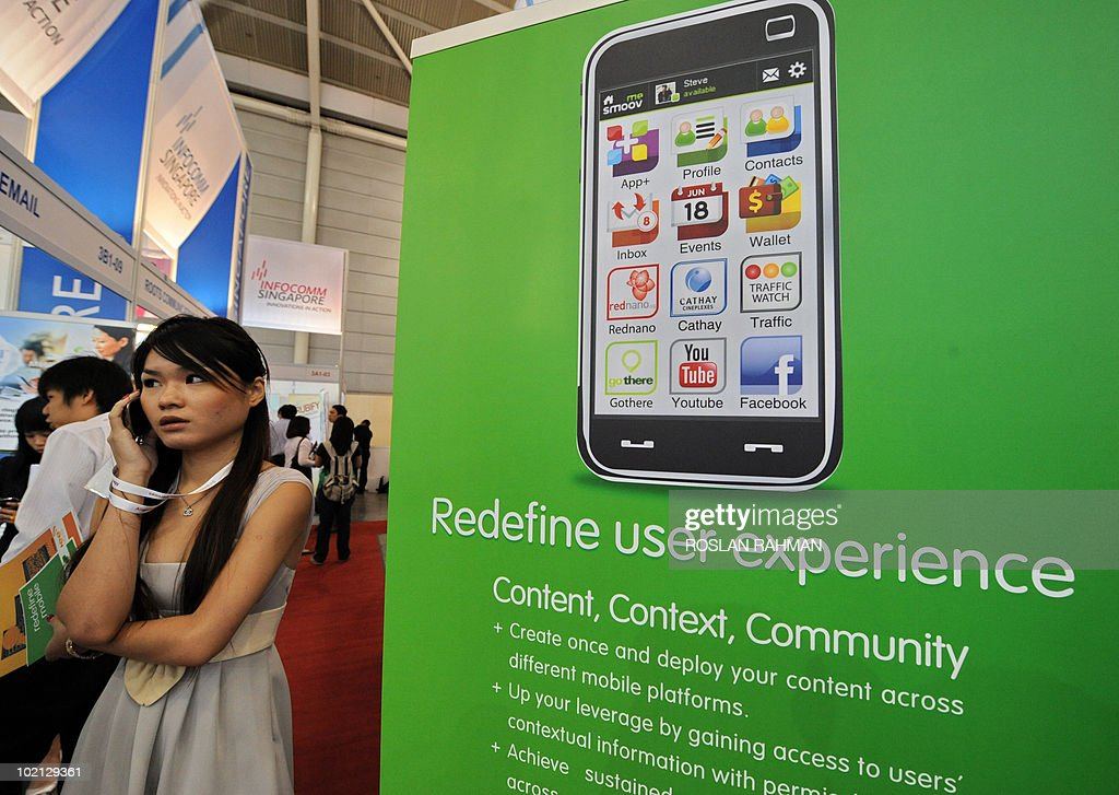 A woman talks on her mobile phone next to a poster displaying smartphone applications at the CommunicAsia 2010 conference and exhibition show in Singapore on June 16, 2010. The exhibition showcases the newest technologies, products and solutions, featuring almost 2000 exhibiting companies from 57 countries and region.