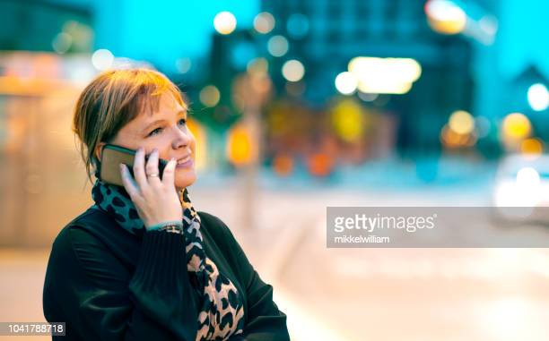 Woman talks on her mobile phone while standing on city street at night