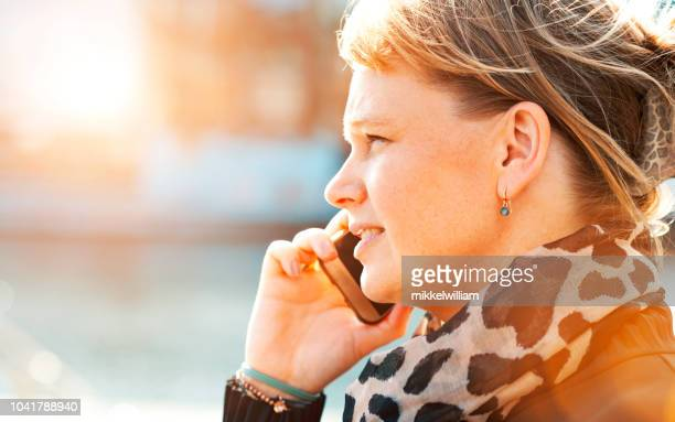 Woman talks on her mobile phone while the sun shines