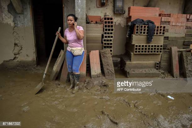 A woman talks on her phone as she holds a shovel to clear the mud from his house after a mudslide due to heavy rains affected Corinto in Cauca...