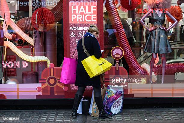 A woman talks on her phone as she stands with her shopping outside a store on Oxford Street on December 23 2016 in London England Shoppers are...
