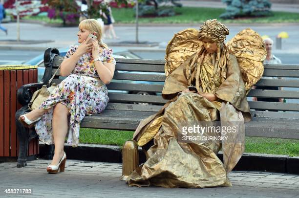 TOPSHOT A woman talks on her phone next to another dressed as an angel sculpture on a bench in the center of Kiev on July 2 2016 / AFP / Sergei...