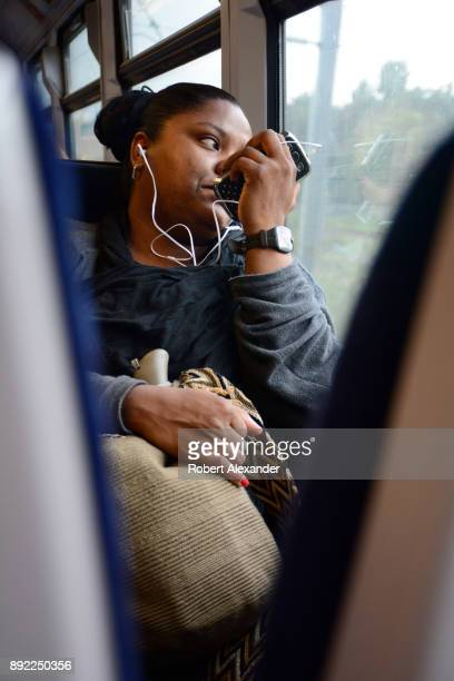 A woman talks on her smartphone as she rides a passenger train from London to Windsor England