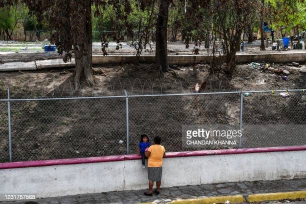 Woman talks to a girl next to the migrant camp that was closed weeks ago by the Mexican Government near the Gateway International Bridge, between the...